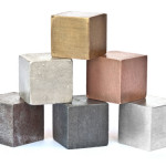 Six common metals imaged on white card. From left to right, bottom row iron zinc aluminum, middle row tin copper, top row brass. Shadow perspective cast by the blocks fades to a pure white background. sRGB color space.